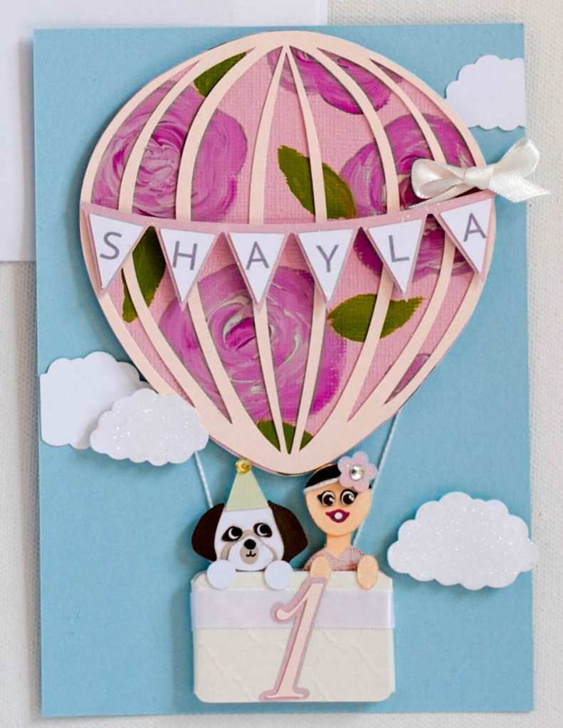 Handmade first birthday invitation featuring hot air ballon, baby, and puppy